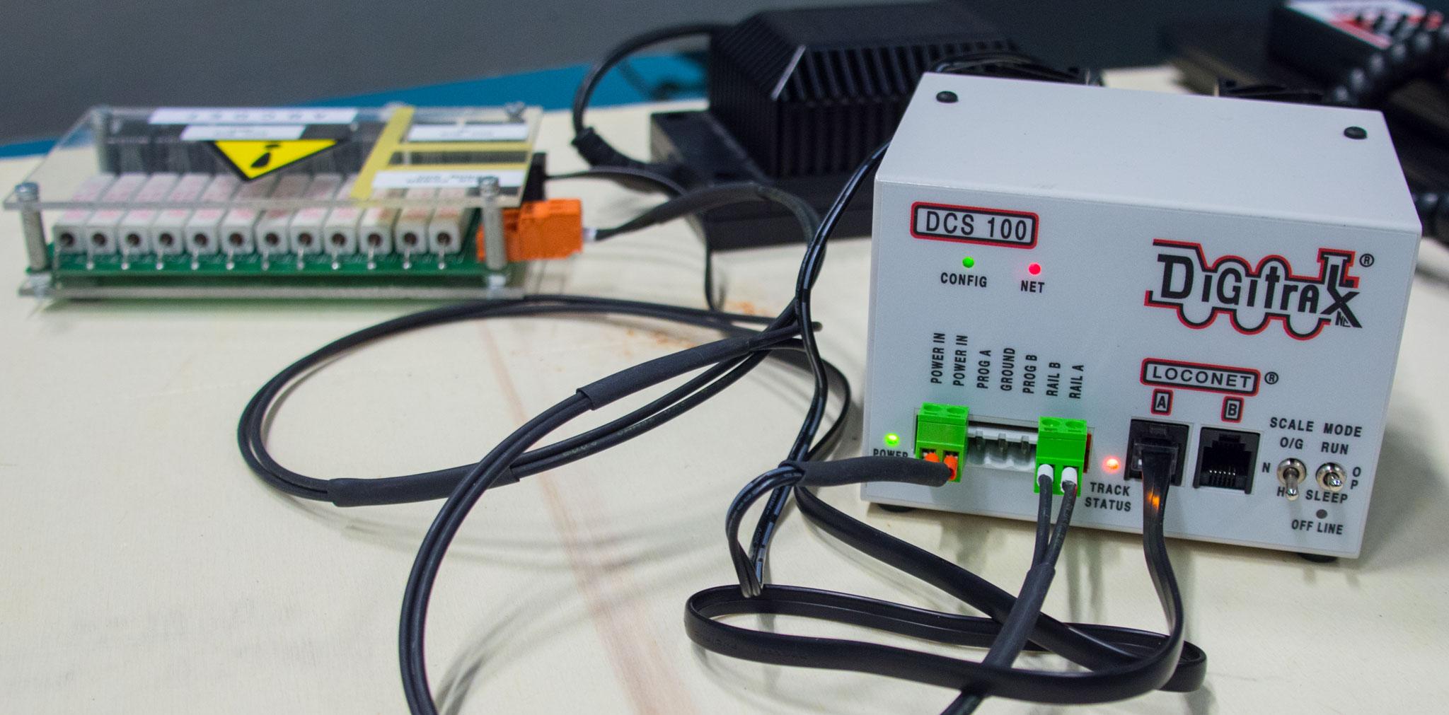 Hjertet i træffet er en Digitrax DCS 100, der sender input fra kørekontrollerne gennem fordeleren i baggrunden ud til boosterne, der sender det videre gennem skinnerne ud til lokomotiverne