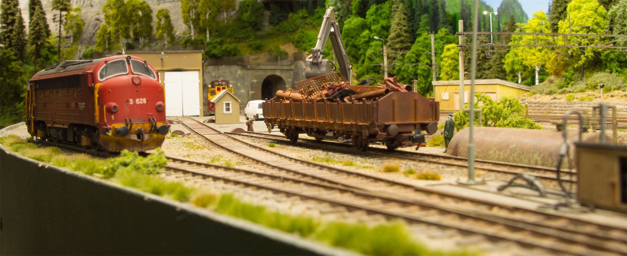 Di3 og åben vogn med skrot på Dalen station