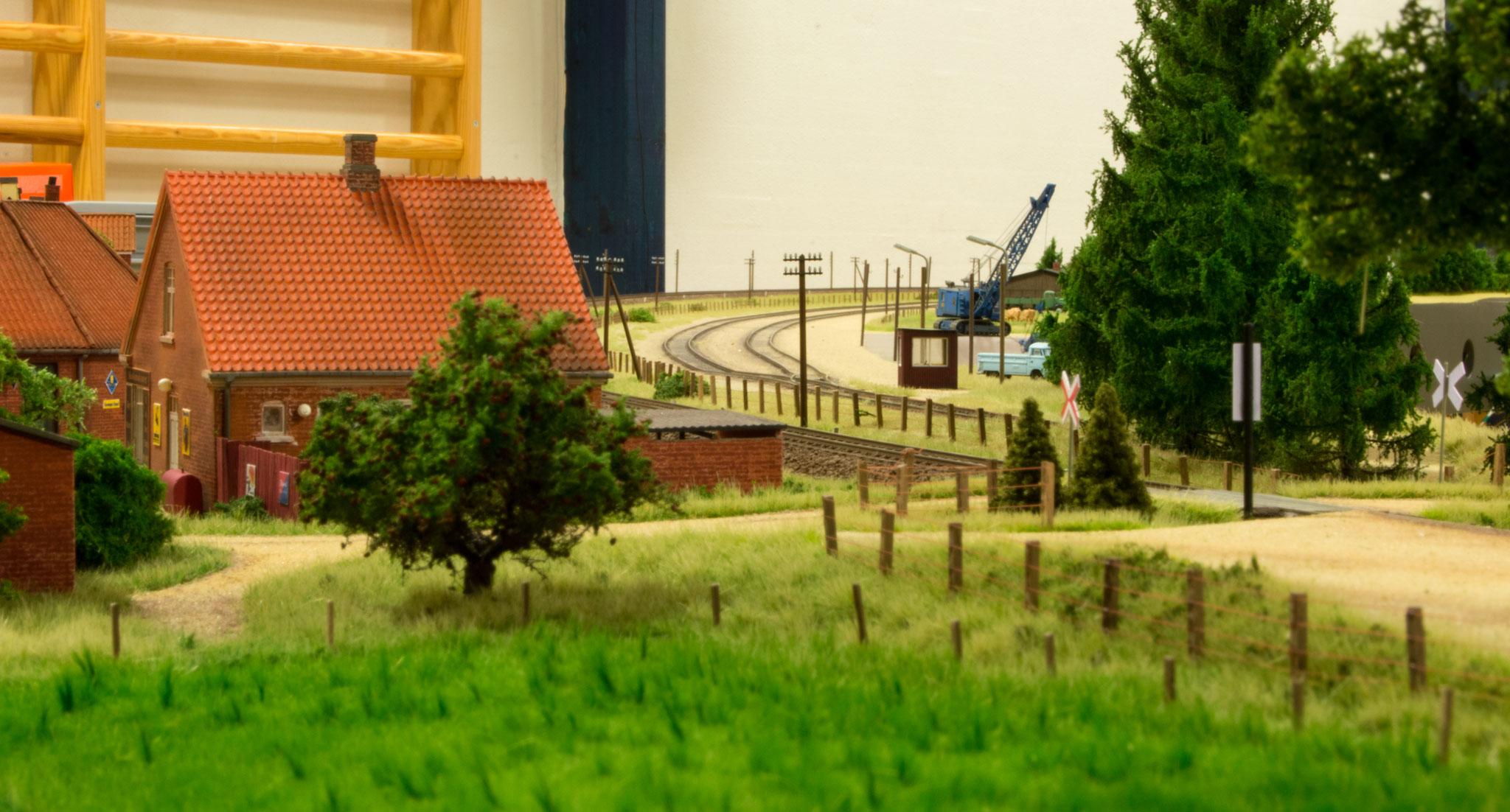 Vue over Søbylund med mark og æbletræ i forgrunden.  I billedets højre side ses jernbaneoverskæringen og gruspladsen ved trinbrættet