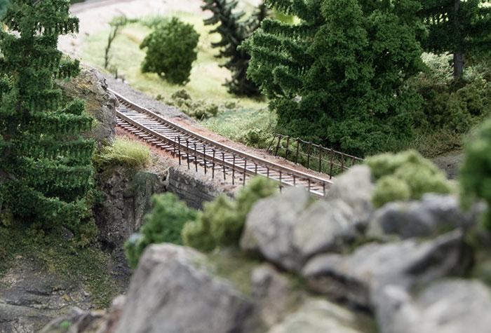 Bro på på klippefyldt modul med bevoksning