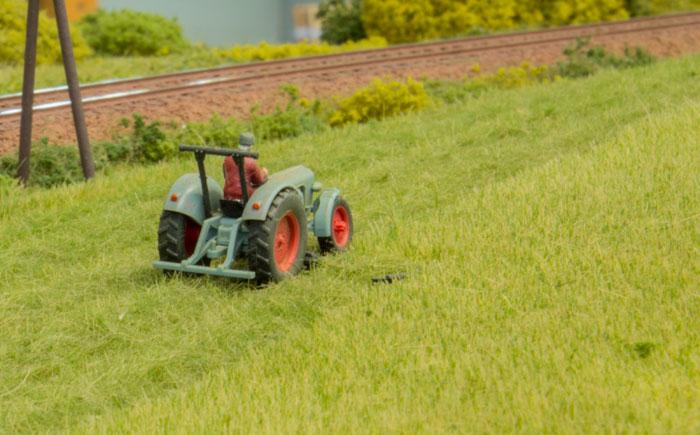 Høstmodul - detalje med landmanden der høster græs med traktor