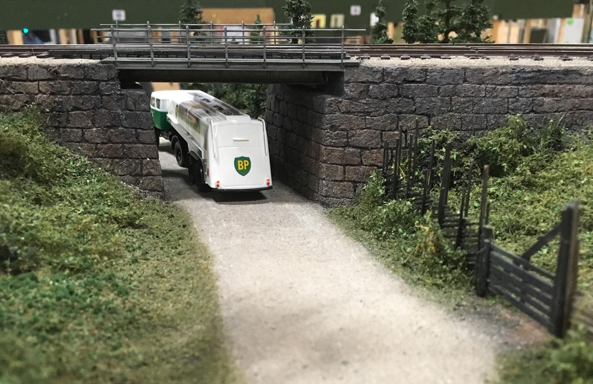 Tankbil under bro med flotte, detaljerede brofæster